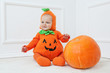 Child in pumpkin suit on white background