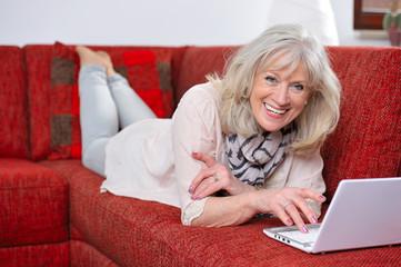 Seniorin liegt entspannt mit Laptop auf der Couch