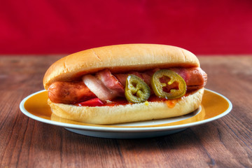 Mexican style hot dog with bacon, salsa, jalapeno
