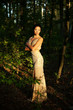 Beautiful young woman in dress in garden on sunset