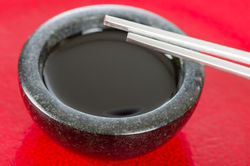 Soy Sauce - Chopsticks resting on a bowl of asian dipping sauce.