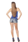 rear view of attractive girl in a short jeans posing on white