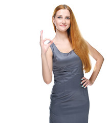 Attractive young woman in a gray business dress. Shows sign okay