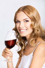 Woman with glass of redwine, on gray