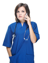 Attractive young nurse with a stethoscope. Talking on a mobile p