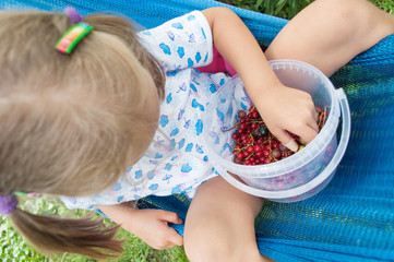 Little girl sitting on hammock and eating berries