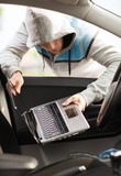 thief stealing laptop from the car