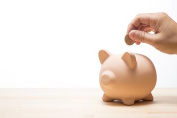 貯金箱にコインを入れる手のアップ