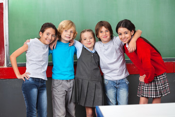 Happy Schoolchildren With Arms Around Standing Together In Class