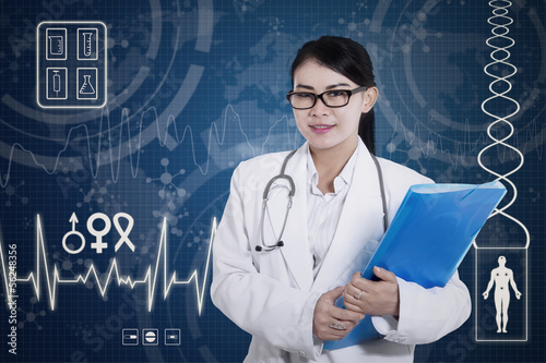 Beautiful female doctor holding folder on digital background