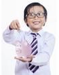 Boy puts the coin into a piggy bank