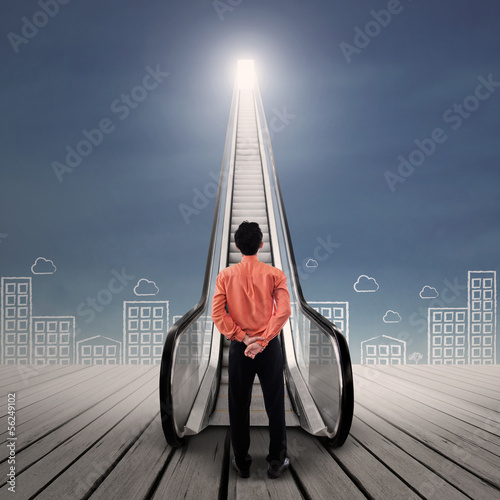 Businessman at escalator under bright sky