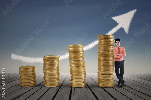Businessman standing next to gold coins growth chart