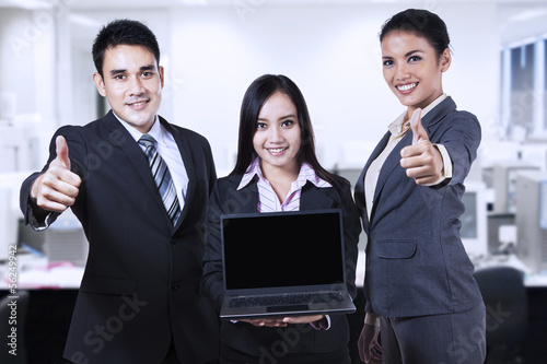 Young business people showing blank screen on laptop