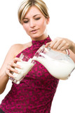 Beautiful woman pour out milk into glass