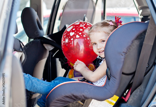 happy toddler girl in car seat