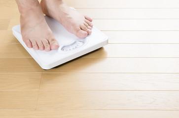 体重計に乗った人物の足のアップ