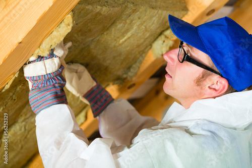 Handwerker schneidet Dämmmaterial