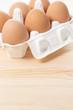 木目の背景に容器にはいった卵