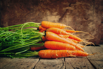 Fresh Organic Carrots lies on wooden background, horizontal, ton