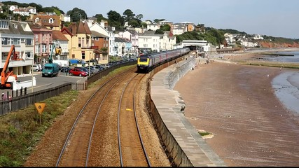 Train approaching coast railway by sea Dawlish Devon England