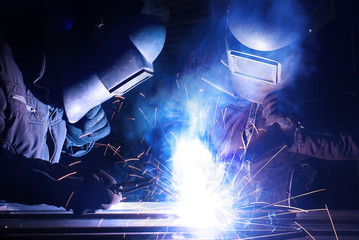 Welders team on the workplace. Construction and manufacturing
