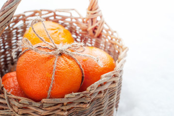 Christmas Oranges in the basket at the snow