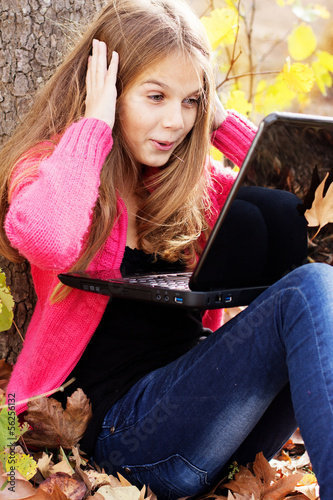 Pretty girl in autumn park with laptop