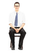 Young male sitting on a wooden chair waiting for job interview