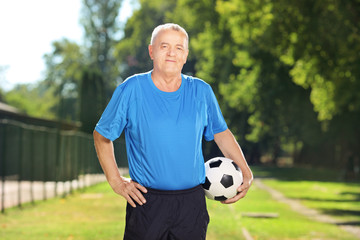 Mature man in sportswear holding a ball in a park