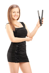 Young beautiful woman in black dress holding a hair straightener