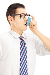 Young man taking asthma treatment