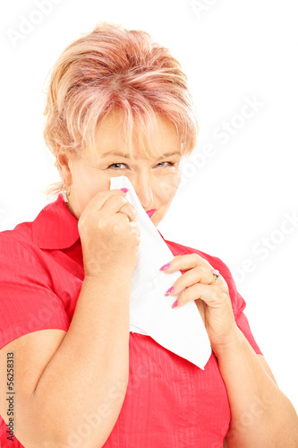 Sad mature woman wiping her eye from crying with tissue