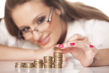 beautiful smiling girl with glasses line up coins in pillars