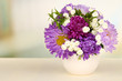 Beautiful bouquet of bright flowers in color vase,
