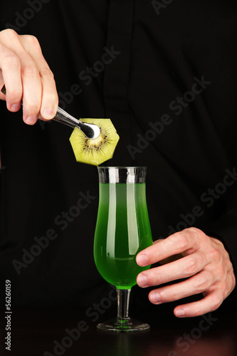 Bartender making and decorating cocktail on close-up