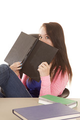 holding book up to face looking over teen