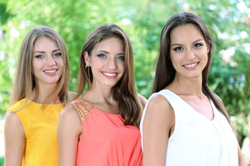 Three beautiful young woman in summer park