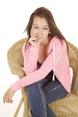 teen girl in wicker jacket sitting in a wicker chair