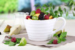Fruit salad in cup on wooden table on nature background