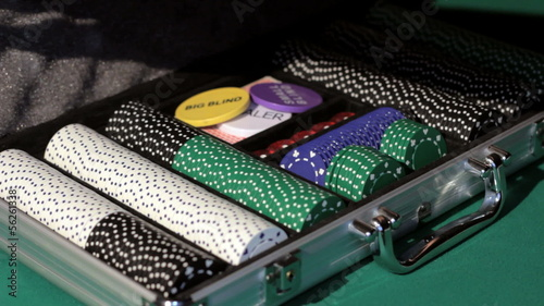Hands open the aluminium suitcase with poker set.