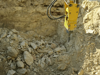 Excavator with Hydraulic hammer demolishes stone