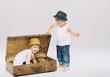 Small boy hiding his elder brother in suitcase