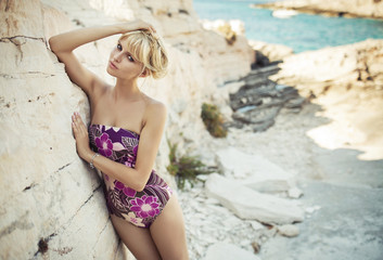 Blonde cutie leaning on the bright rock
