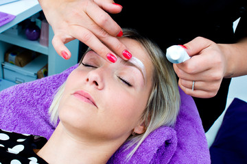 beautician putting skin cream on woman face