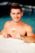 Handsome man in the pool toasting with champagne