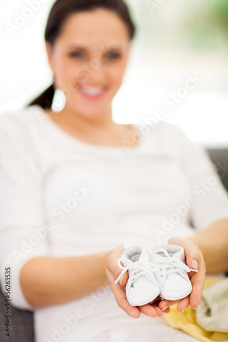 mother to be holding baby shoes