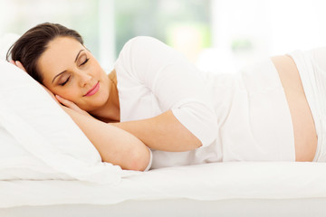 young pregnant woman sleeping in bed