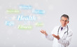 Clinical doctor pointing to health and fitness collection of wor
