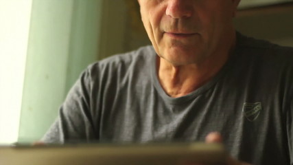 Portrait of a man at the age with Tablet PC